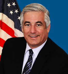 Profile Picture of Dr. West in a black suit with a purple tie sitting in front of a draped American flag.