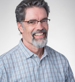 Profile picture of Joe Burke with short brown hair, prescription glasses, silver goatee, and checkerboard collared shirt